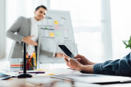 Photo for Selective focus of ux designer looking at colleague near whiteboard with layouts in office - Royalty Free Image