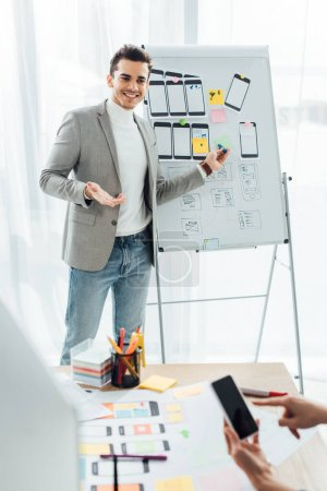 Photo for Selective focus of smiling ux designer near whiteboard with templates looking at colleague pointing on smartphone in office - Royalty Free Image