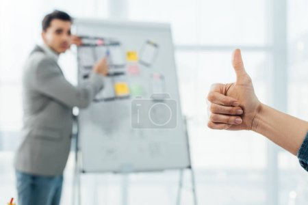 Photo for Selective focus of ux designer showing like sign to developer near whiteboard in office - Royalty Free Image