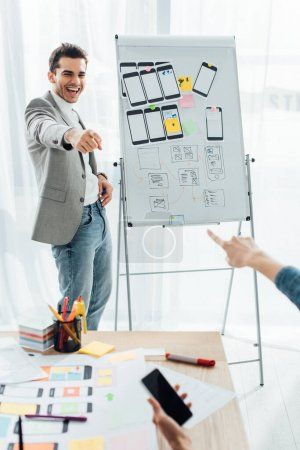 Photo pour Selective focus of smiling ux designer near whiteboard with templates pointing on colleague with smartphone in office - image libre de droit