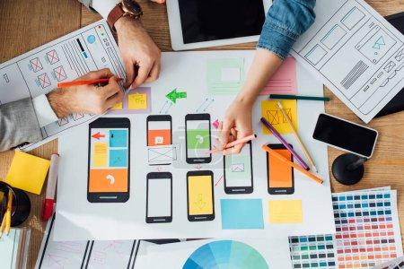 Photo pour Vue du dessus des concepteurs interface d'application créative pour la conception de l'expérience utilisateur près des mises en page et des appareils numériques sur la table - image libre de droit