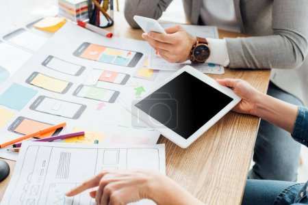 Photo for Cropped view of ux designers using gadgets near mobile frameworks on table isolated on grey - Royalty Free Image