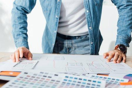 Photo pour Vue agrandie de ux designer à l'aide de croquis et de palettes de couleurs sur la table au bureau - image libre de droit
