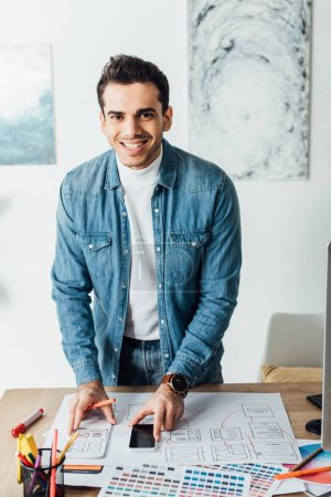 Photo pour Smiling designer looking at camera while working with ux wireframe sketches, color palettes and smartphone on table - image libre de droit