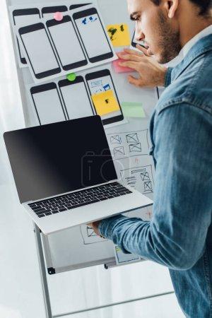 Photo pour Conception d'Ux utilisant un ordinateur portable près de modèles de site Web sur tableau blanc au bureau - image libre de droit