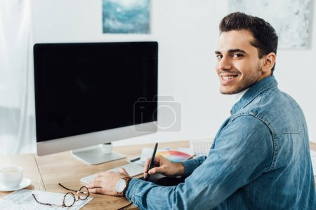 Photo pour Designer smiling at camera while working on project of user experience design near computer and graphics tablet on table - image libre de droit