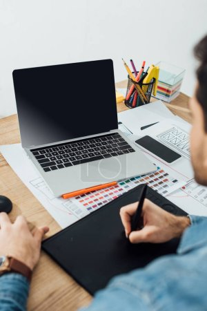 Photo for Selective focus of developer using laptop and graphics tablet near sketches of user experience design and smartphone on table isolated on grey - Royalty Free Image