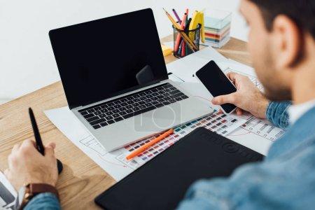 Photo pour Mise au point sélective du concepteur au moyen d'un smartphone près de l'ordinateur portatif, tablette graphique et mise en page avec croquis sur table sur fond gris - image libre de droit