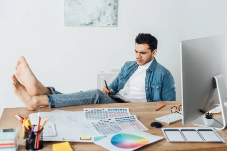 Barefoot designer using graphics tablet near sketches of user experience design and computer on table