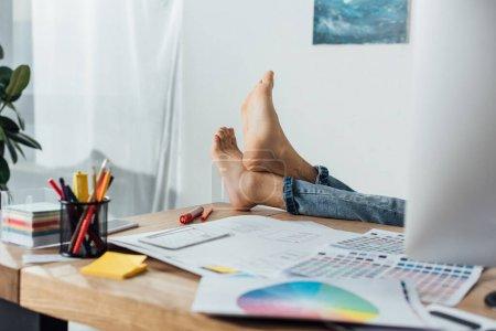 Photo pour Vue recadrée du concepteur pieds nus assis à table avec ordinateur et mises en page de la conception de l'expérience utilisateur - image libre de droit