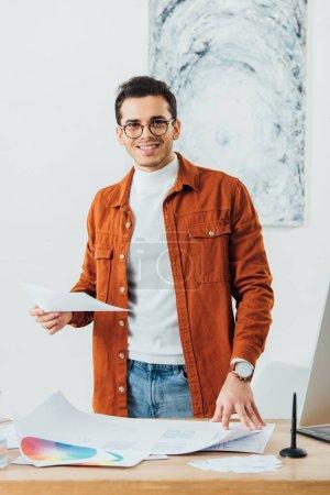 Foto de El diseñador Ux sonríe en la cámara mientras trabaja con círculos de color y plantillas de diseño de experiencia de usuario en la mesa. - Imagen libre de derechos
