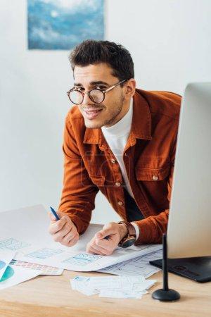 Photo pour Focus sélectif du concepteur ux souriant à la caméra près de l'écran de l'ordinateur et des esquisses filaires du site Web sur la table - image libre de droit