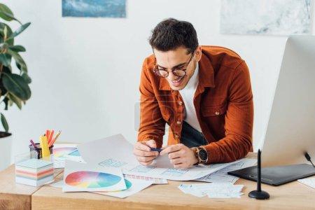 Photo pour Concepteur ux joyeux travaillant avec des esquisses et des mises en page wireframe site près de moniteur d'ordinateur et tablette graphique sur la table - image libre de droit