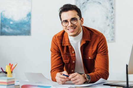 Photo pour Designer créatif souriant à la caméra tout en travaillant sur le projet de conception de l'expérience utilisateur à la table dans le bureau - image libre de droit