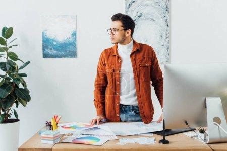 Photo pour Designer regardant loin près des gadgets, des cercles de couleur et des mises en page de la conception de l'expérience utilisateur sur la table - image libre de droit