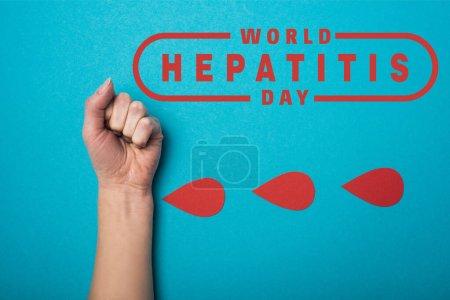 Photo pour Haut de la page Gouttes de sang près du poing d'une femme sur fond bleu, illustration de la journée mondiale de l'hépatite - image libre de droit