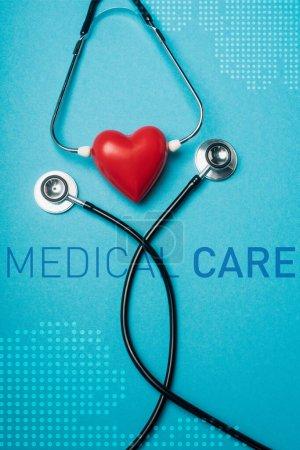 Photo pour Vue du dessus du coeur rouge décoratif avec stéthoscope noir sur fond bleu, illustration de soins médicaux - image libre de droit