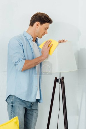 Photo pour Vue latérale d'un homme nettoyant lampadaire avec chiffon dans le salon - image libre de droit