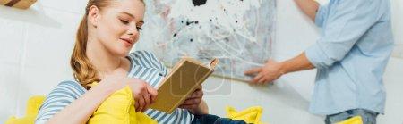 Photo pour Concentration sélective de livre de lecture de femme près du petit ami tenant la peinture dans le salon, plan panoramique - image libre de droit