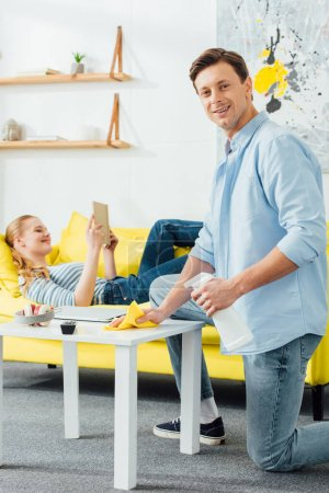 Photo pour Side view of smiling man with rag and detergent cleaning coffee table near girlfriend with book on dich at home - image libre de droit