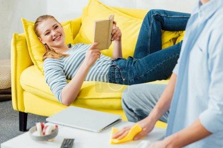 Foto de Enfoque selectivo de mujer sonriente con libro sobre la mesa de café de limpieza novio en el salón. - Imagen libre de derechos