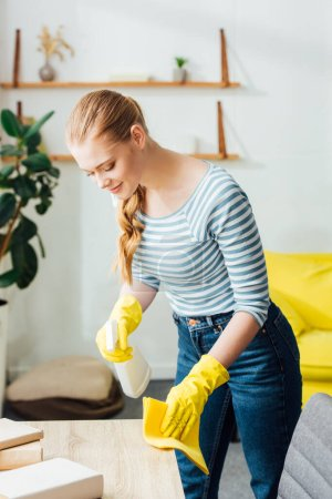 Photo for Attractive woman in rubber gloves holding rag and detergent while cleaning table in living room - Royalty Free Image
