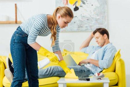 Photo pour Vue latérale de la fille de nettoyage table basse avec détergent et chiffon près du petit ami en utilisant un ordinateur portable sur le canapé dans le salon - image libre de droit