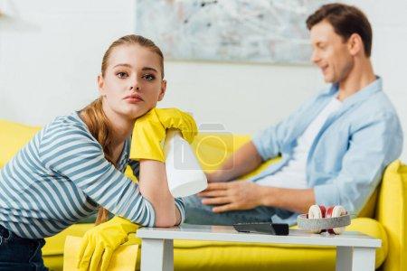 Photo pour Focus sélective de la femme avec détergent et chiffon regardant la caméra près du petit ami en utilisant un ordinateur portable sur le divan dans le salon - image libre de droit