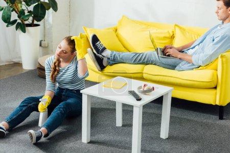 Photo pour Femme épuisée avec des produits de nettoyage assise par terre près de son petit ami avec un ordinateur portable sur le divan dans le salon - image libre de droit