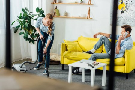 Photo for Selective focus of man talking on smartphone while girlfriend cleaning carpet with vacuum cleaner in living room - Royalty Free Image
