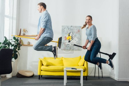 Photo for Side view of cheerful couple levitating on brooms in living room - Royalty Free Image