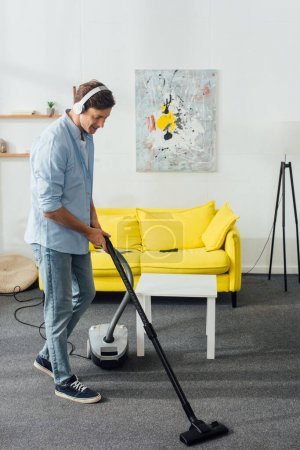 Photo for Side view of smiling man in headphones cleaning carpet with vacuum cleaner at home - Royalty Free Image