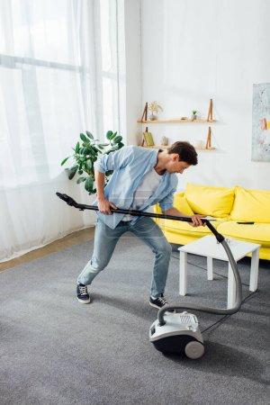 Photo pour Homme tenant brosse d'aspirateur tout en nettoyant dans le salon - image libre de droit