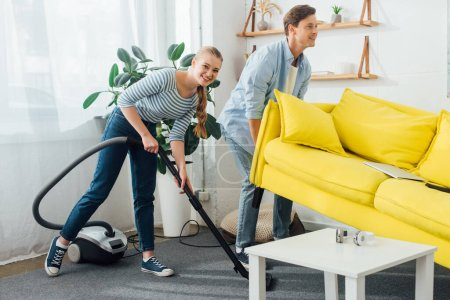 Photo for Smiling man lifting up couch near girlfriend with vacuum cleaner in living room - Royalty Free Image