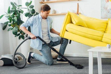 Photo pour Vue latérale de l'homme soulevant canapé tout en nettoyant le tapis avec aspirateur - image libre de droit