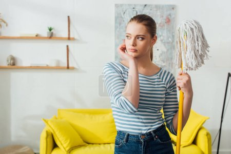 Pensive woman holding mop and looking away at home
