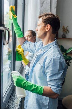 Photo pour Vue latérale d'un jeune couple nettoyant une fenêtre à la maison - image libre de droit