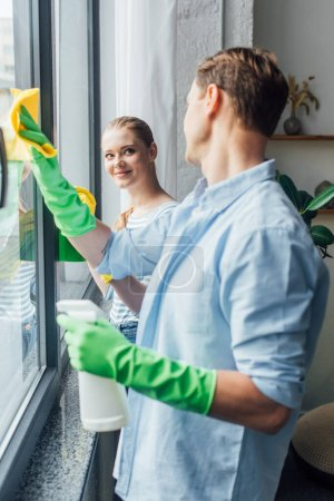 Photo for Side view of couple smiling at each other while cleaning glass of window in living room - Royalty Free Image
