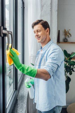 Photo pour Vue latérale de l'homme avec bouteille de détergent et chiffon souriant tout en nettoyant le verre de la fenêtre à la maison - image libre de droit