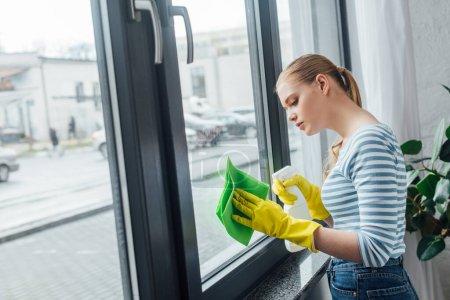 Photo pour Vue latérale de la femme qui utilise du chiffon et du détergent pour nettoyer sa fenêtre à la maison - image libre de droit