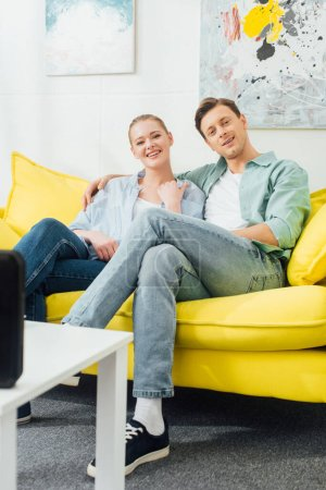 Smiling couple looking at camera near wireless speaker on coffee table in living room