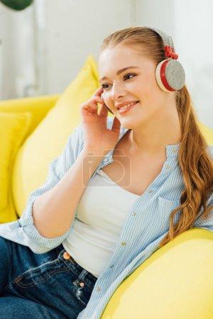 Piękna uśmiechnięta kobieta słuchająca muzyki w słuchawkach w domu