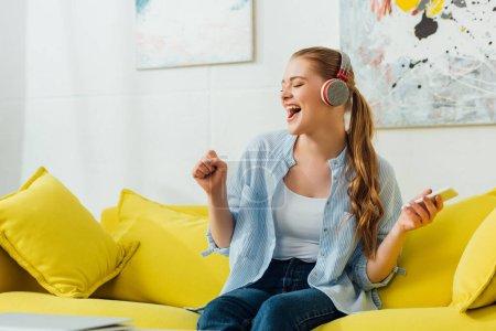Photo pour Fille gaie dans les écouteurs chantant et tenant smartphone sur le canapé à la maison - image libre de droit