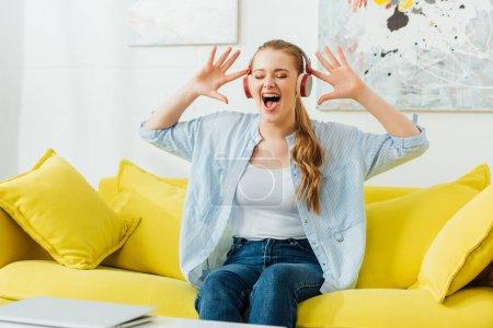 Photo pour Belle femme dans les écouteurs chantant sur canapé dans le salon - image libre de droit