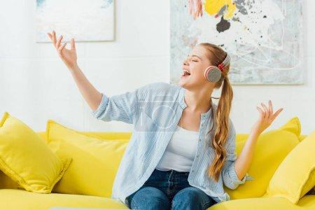 Photo pour Belle femme chantant en écoutant de la musique dans les écouteurs sur le canapé à la maison - image libre de droit