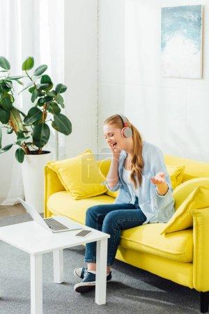 Photo pour Vue latérale d'une belle femme dans un casque chantant près d'un ordinateur portable et d'un smartphone sur une table basse - image libre de droit