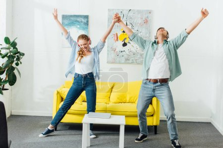 Positive couple in headphones dancing near laptop on coffee table in living room