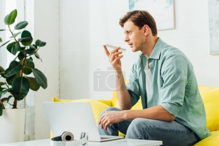 Photo pour Side view of man talking on smartphone near headphones and laptop on coffee table in living room. - image libre de droit