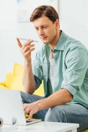 Photo pour Orientation sélective de l'homme à l'aide d'un téléphone intelligent et d'un ordinateur portable sur une table basse dans le salon - image libre de droit