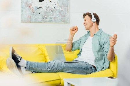 Photo pour Vue latérale d'un homme souriant dans un casque d'écoute en train de chanter assis avec un ordinateur portable sur un canapé - image libre de droit